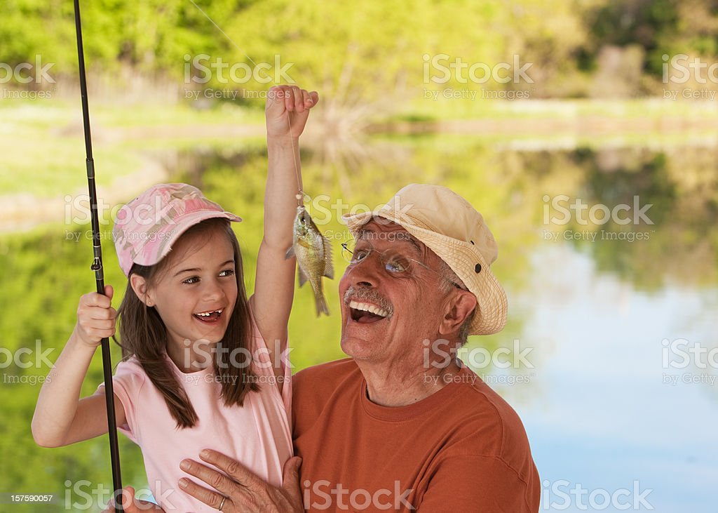 Little Girl Showing Fish to Grandfather stock photo
