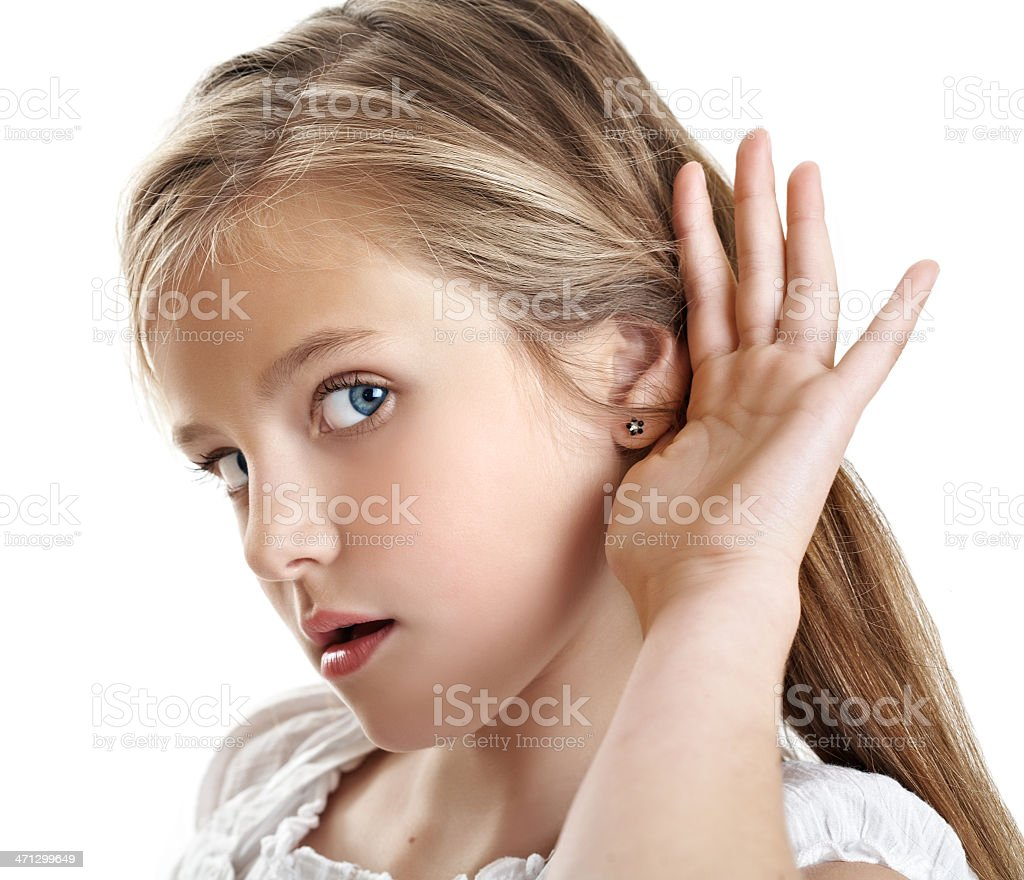 Little girl showing that she is listening stock photo