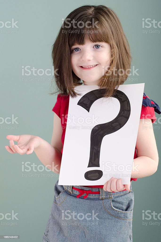 little girl shrugs while holding a question mark stock photo