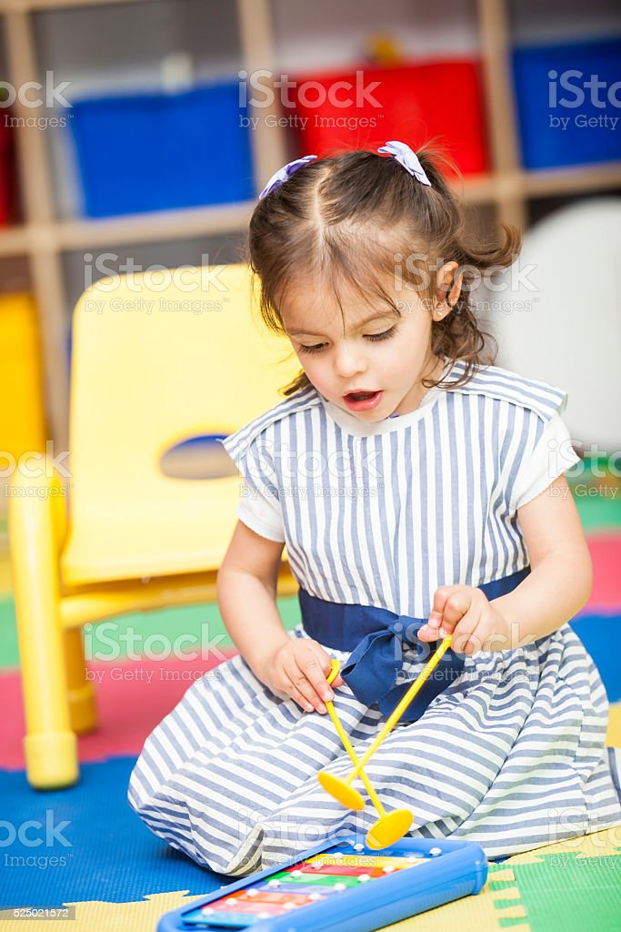 Little girl singing and playing a xylophone stock photo