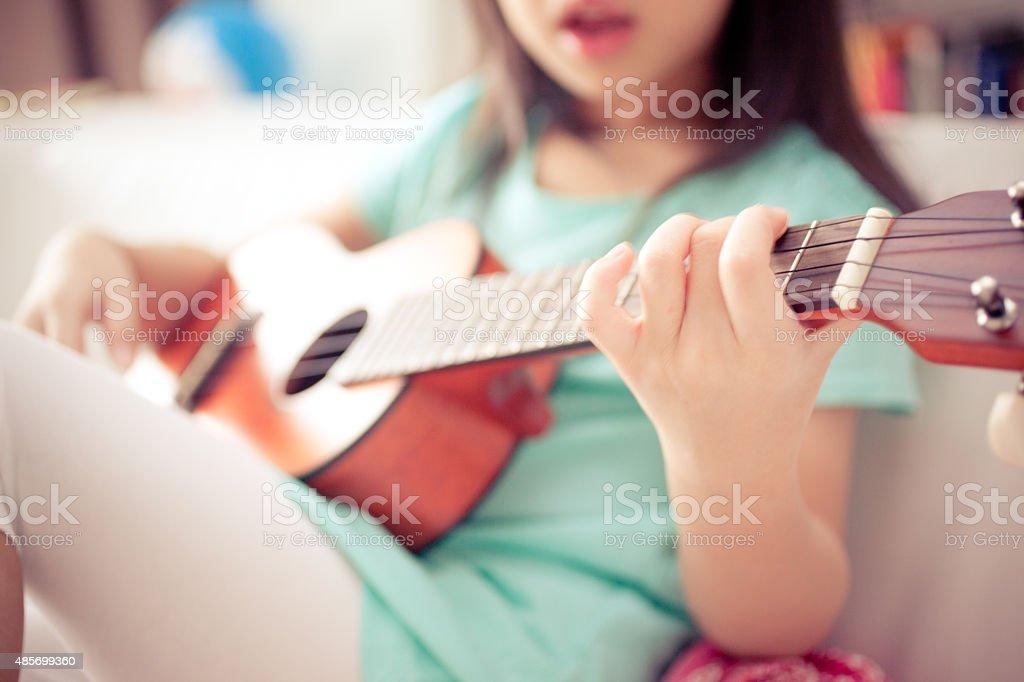 Little Girl Singing and Playing Ukulele on Couch stock photo
