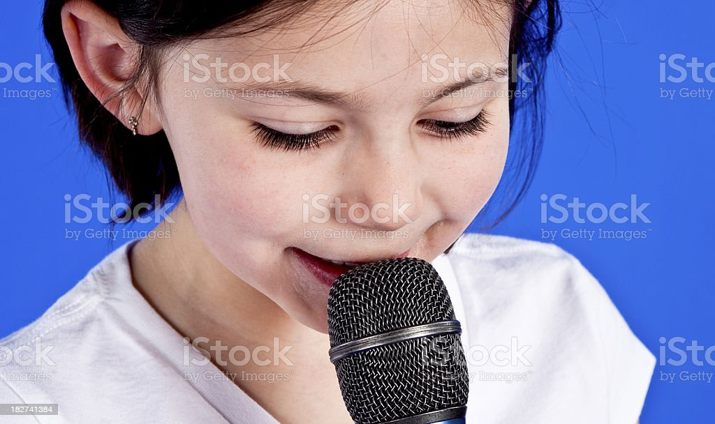 little girl singing in a microphone stock photo