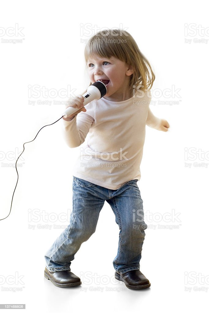 Little girl singing on a microphone stock photo