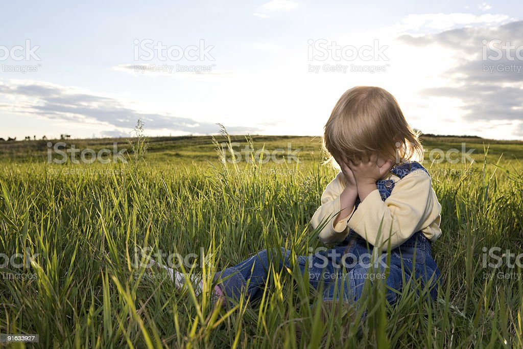 little girl sit in grass stock photo