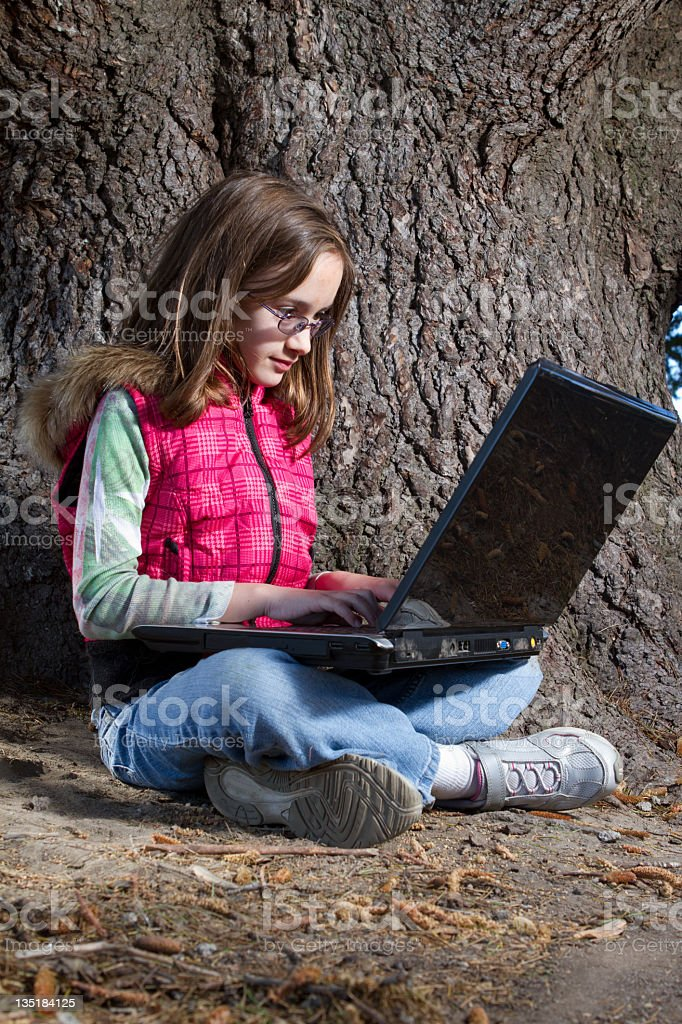LIttle girl sits under a tree with her Laptop. stock photo