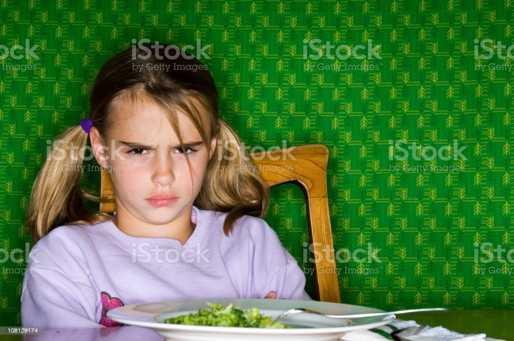 Little Girl Sitting at Dinner Table with Plate of Broccoli stock photo