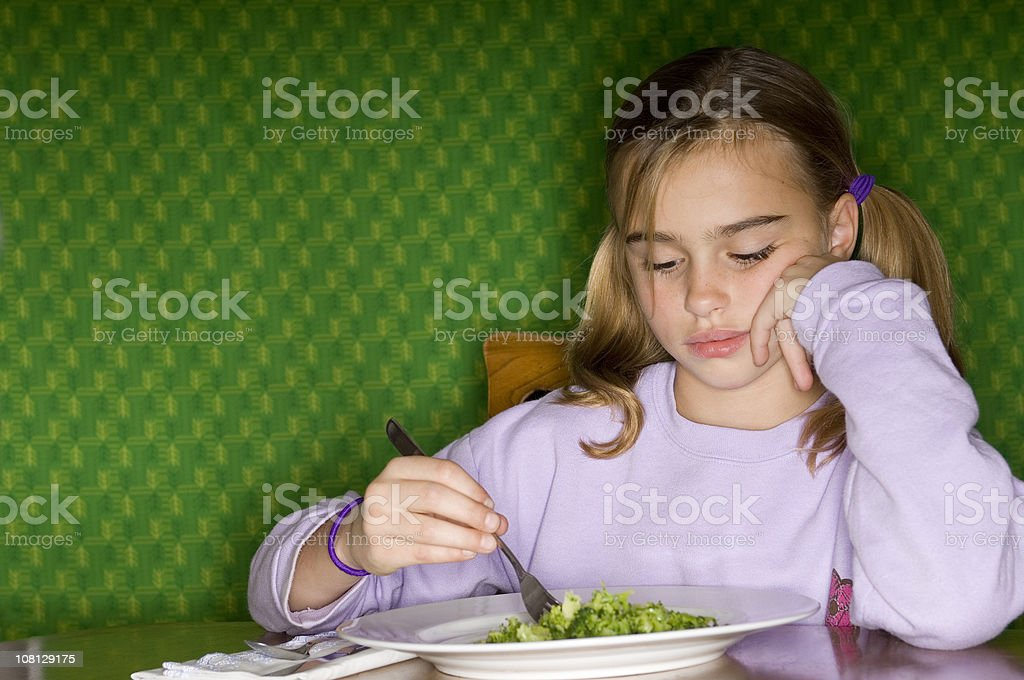 Little Girl Sitting at Dinner Table with Plate of Broccoli royalty-free stock photo