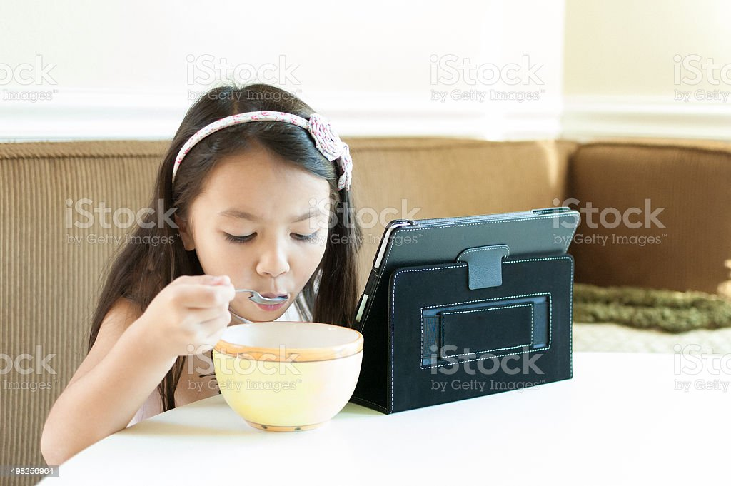 Little girl sitting at kitchen table with iPad eating cereal stock photo