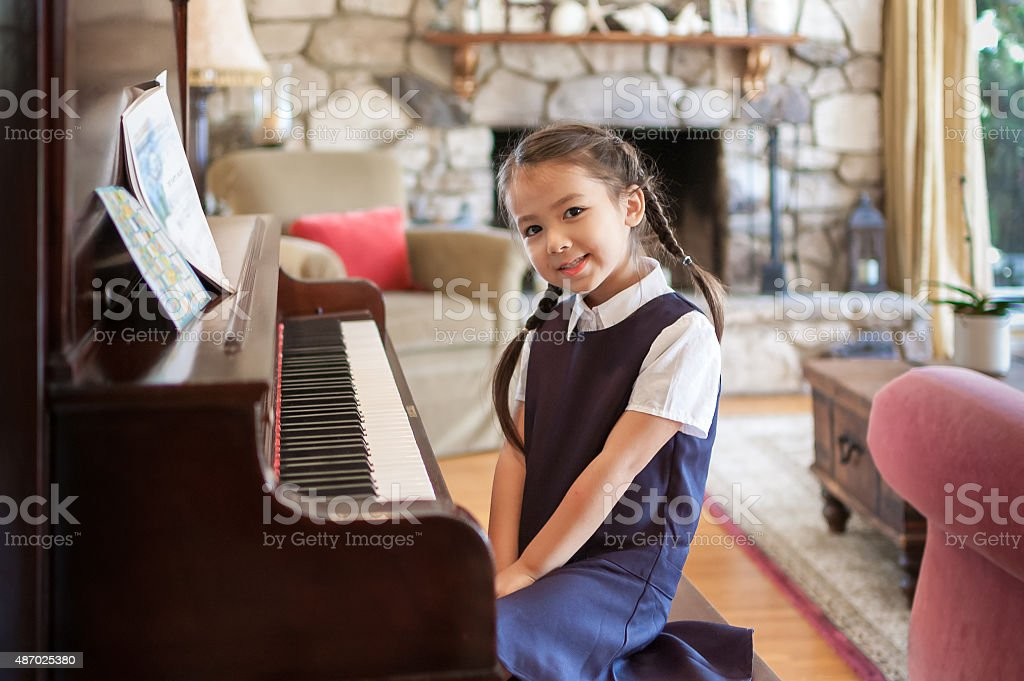 Little girl sitting at the piano at home stock photo