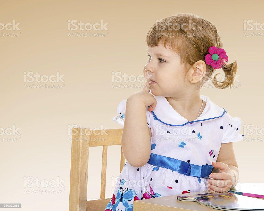 Petite fille assise à la table. photo libre de droits