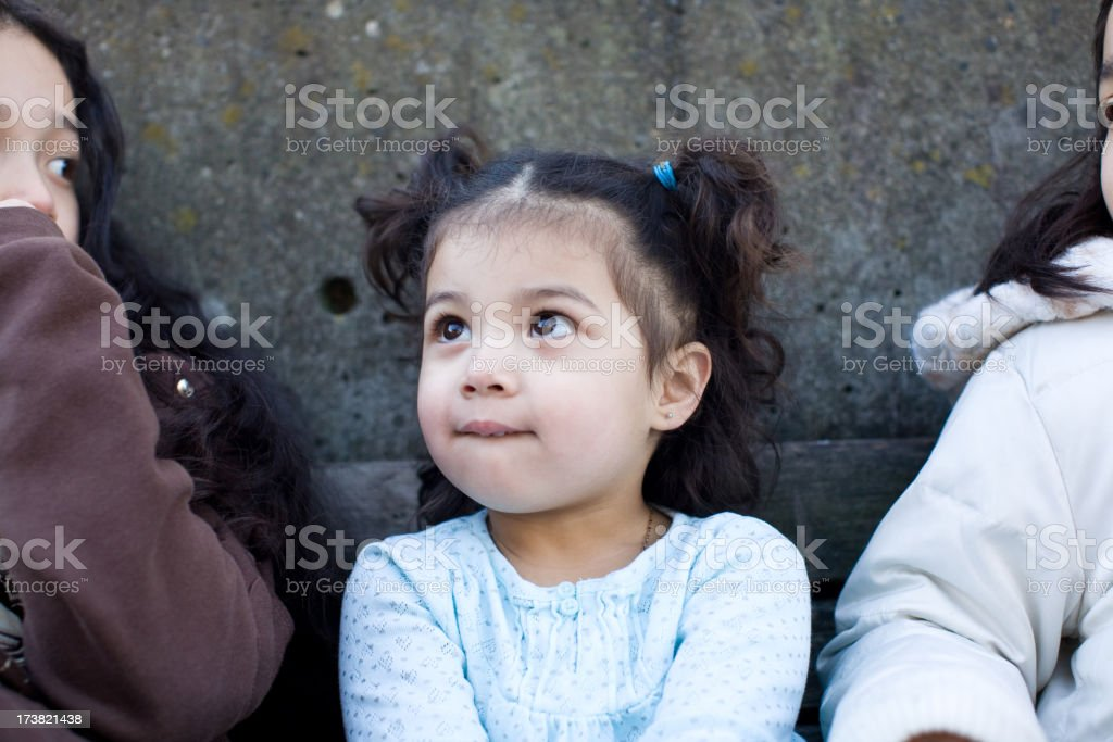 Little girl sitting between her sisters at the park royalty-free stock photo