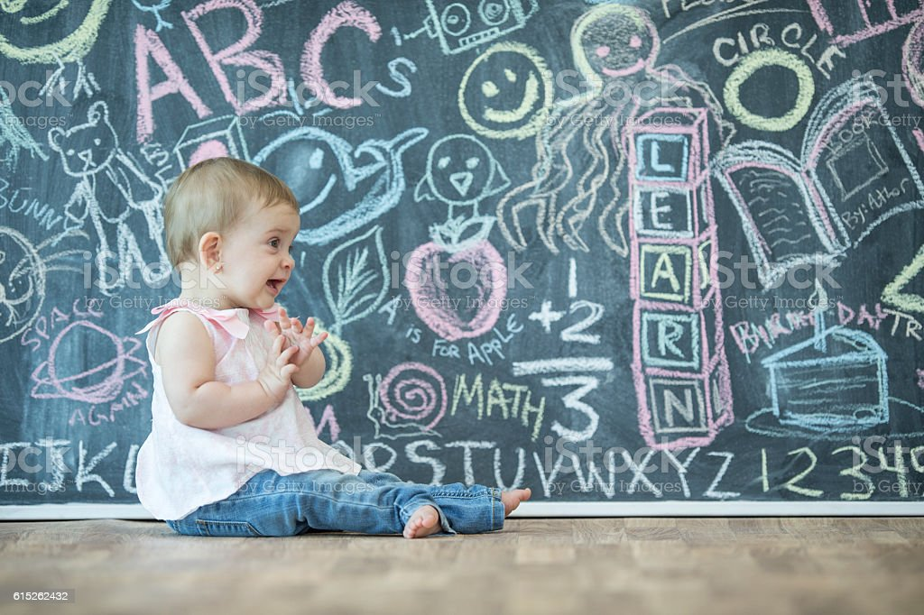 Little Girl Sitting by a Chalk Board stock photo