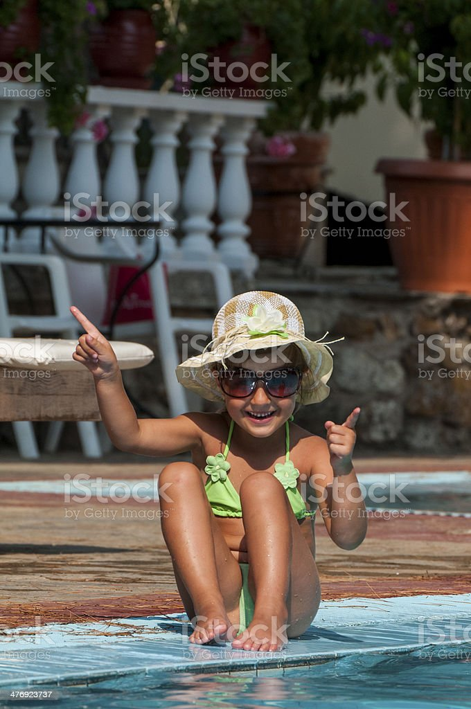 Little Girl Sitting By Edge of Pool on Sunny Day stock photo
