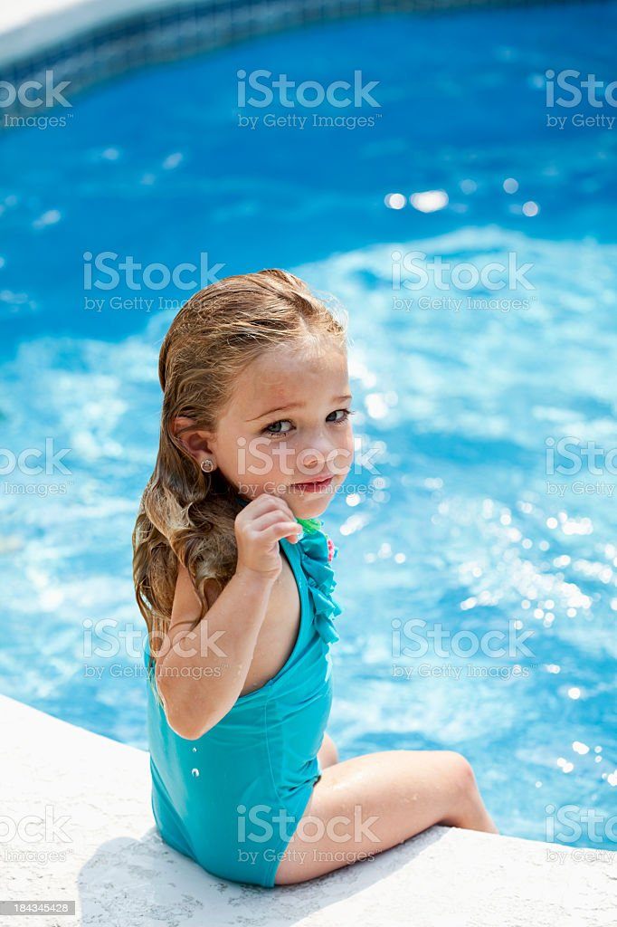 Little girl sitting by pool stock photo