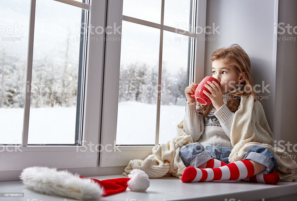 little girl sitting by the window stock photo