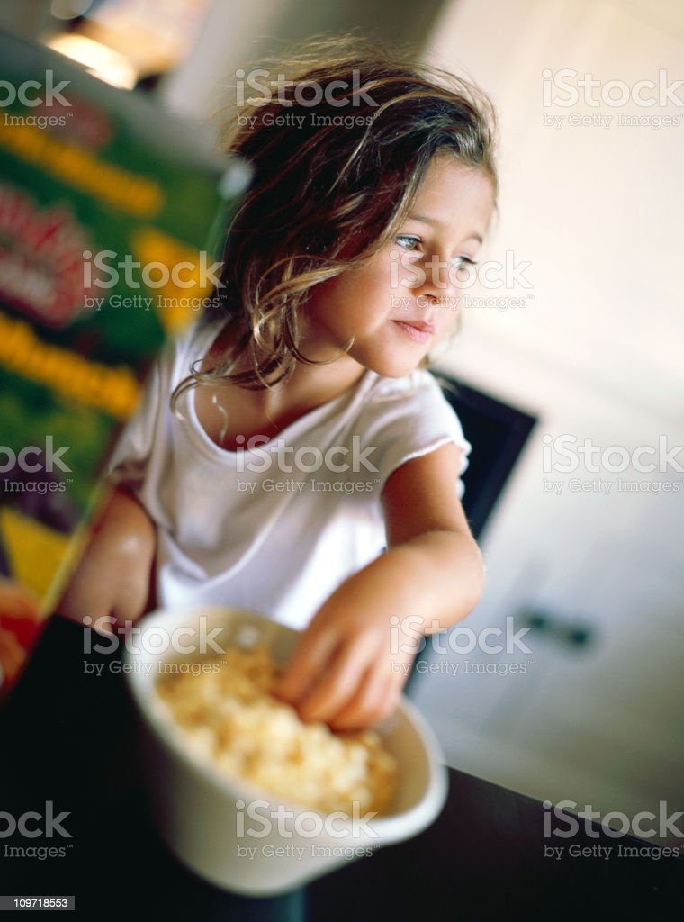 Little Girl Sitting in Kitchen and Eating Cereal From Bowl royalty-free stock photo