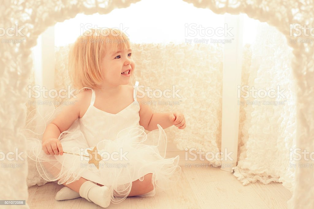 Little Girl Sitting In Playhouse stock photo