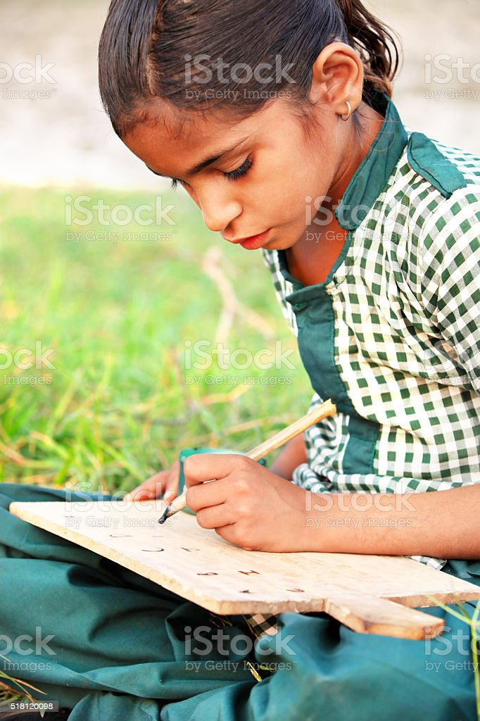 Little girl sitting in the field & writing stock photo