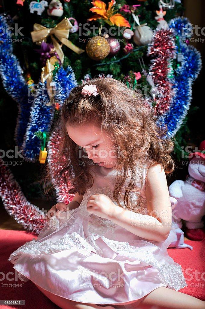 little girl sitting near the Christmas tree stock photo