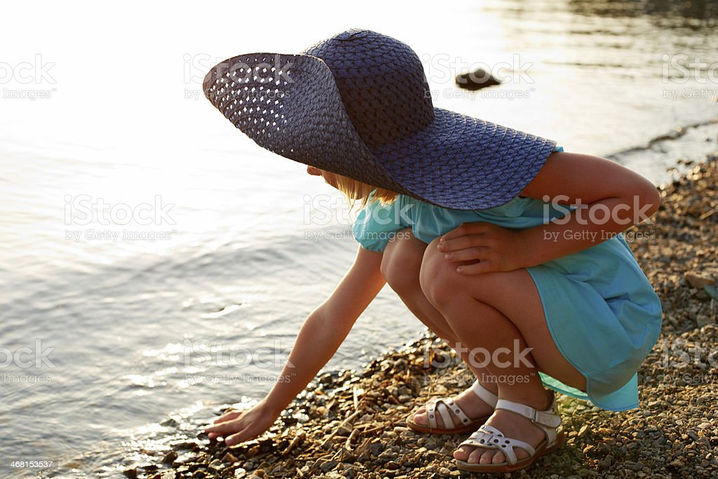Little girl sitting near the water royalty-free stock photo