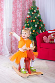 Little girl sitting on a toy horse near christmas tree