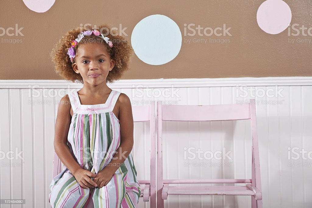 Little girl sitting on chair stock photo