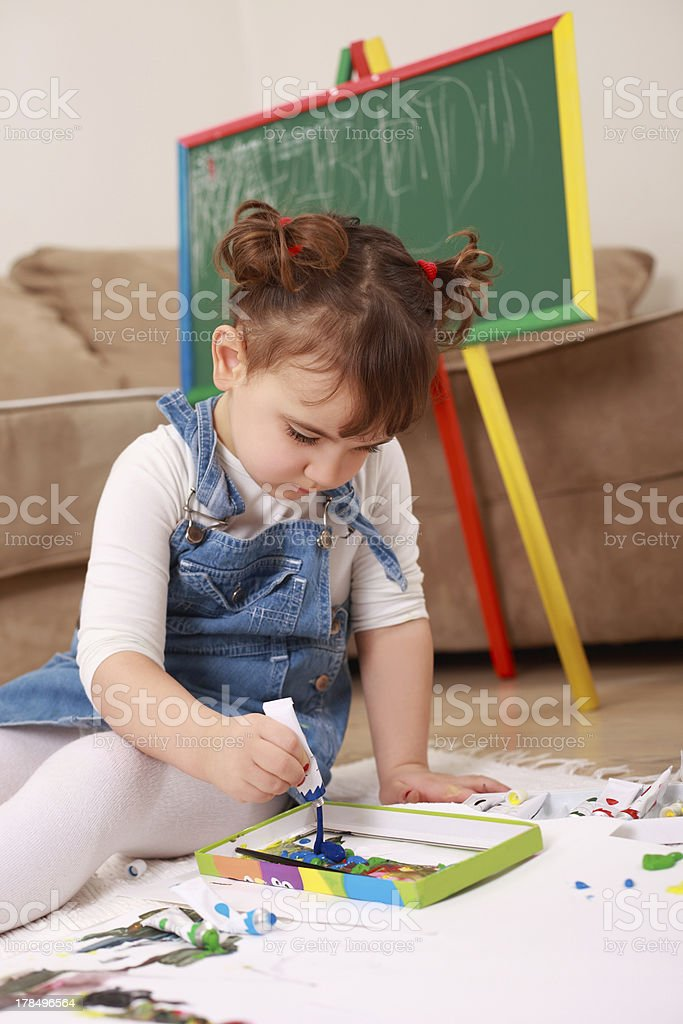 Little girl sitting on floor and painting with tempera royalty-free stock photo