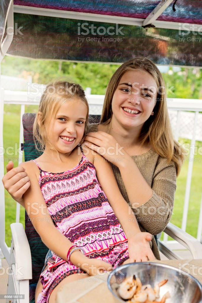 Little girl sitting on lap of sister at summer BBQ. stock photo