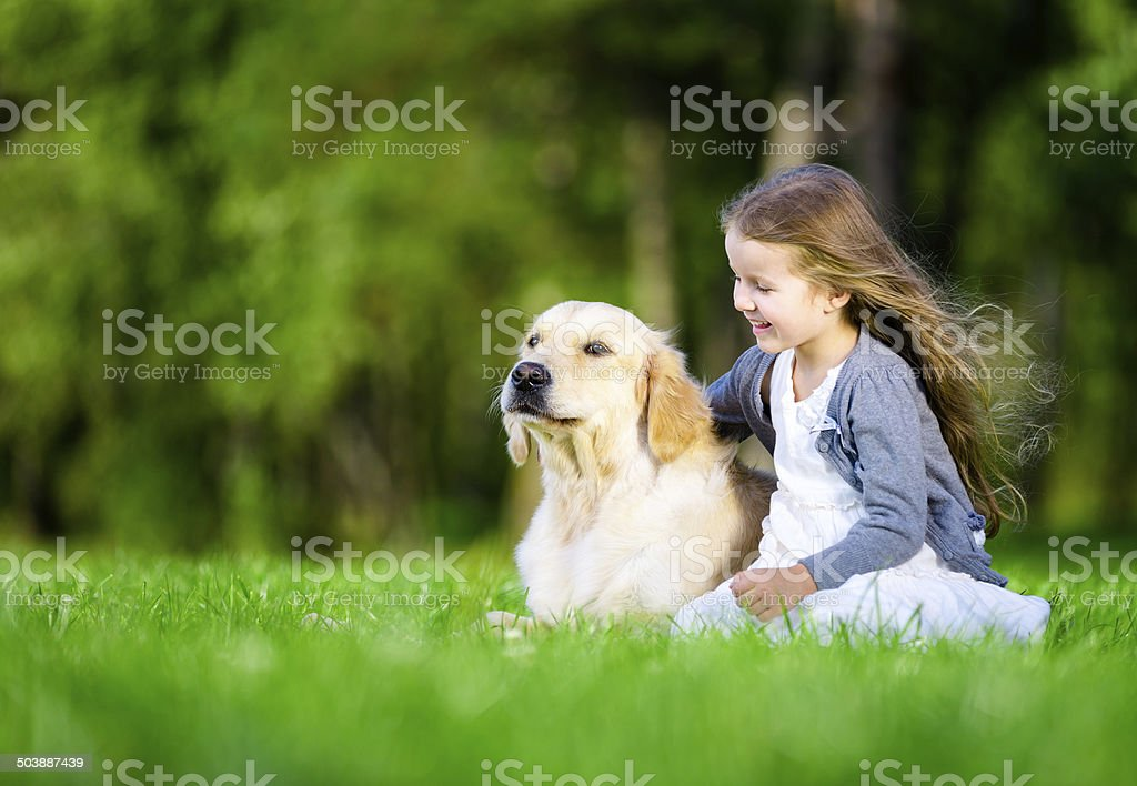 Little girl sitting on the grass with dog stock photo