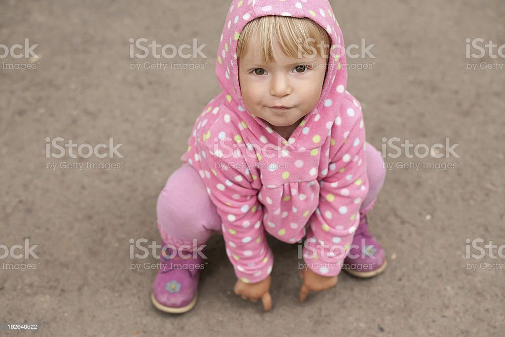 little girl sitting on the ground royalty-free stock photo