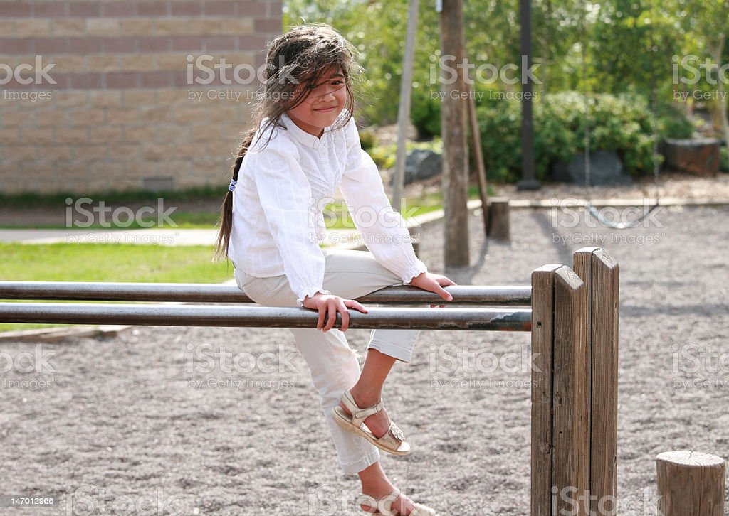 Little girl sitting on top of parallel bars at playground royalty-free stock photo
