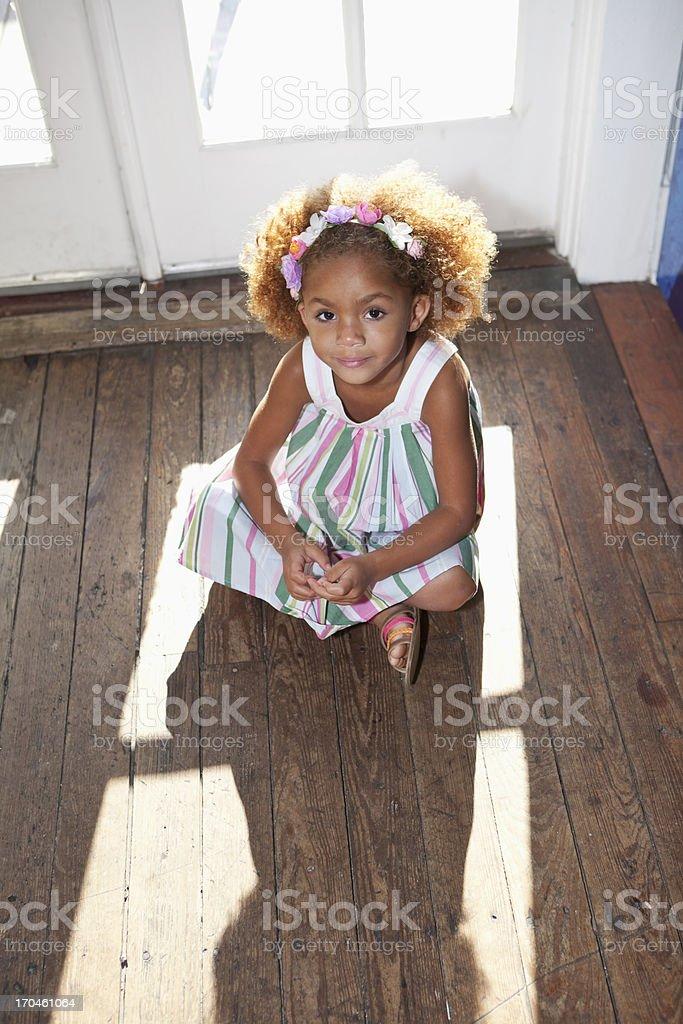 Little girl sitting on wood floor stock photo
