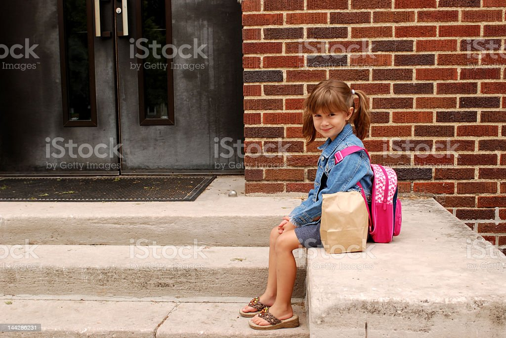 Little girl sitting outside with her backpack and snacks  stock photo