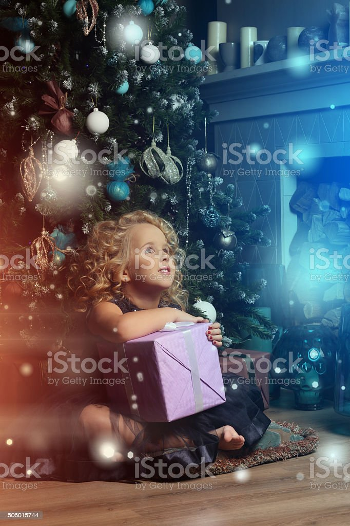 Little girl sitting with a gift on the pillow stock photo