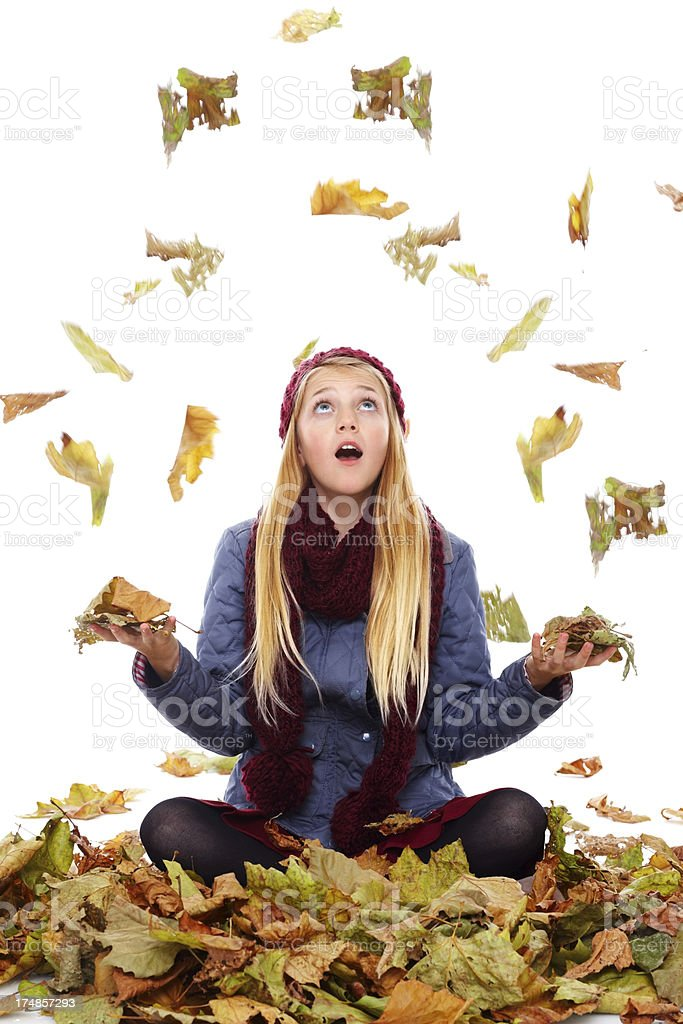 Little girl sitting  with autumn leaves falling around royalty-free stock photo