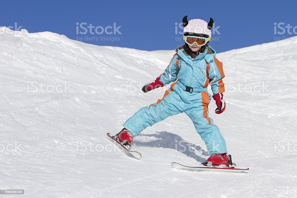 Little girl skiing downhill stock photo