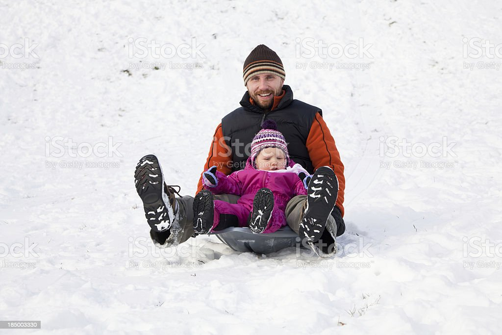 Little girl sledding with dad stock photo