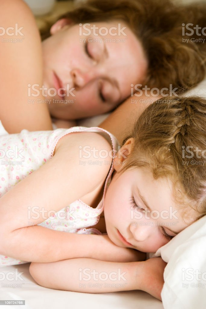 Little Girl Sleeping on Bed With Mother in Background royalty-free stock photo