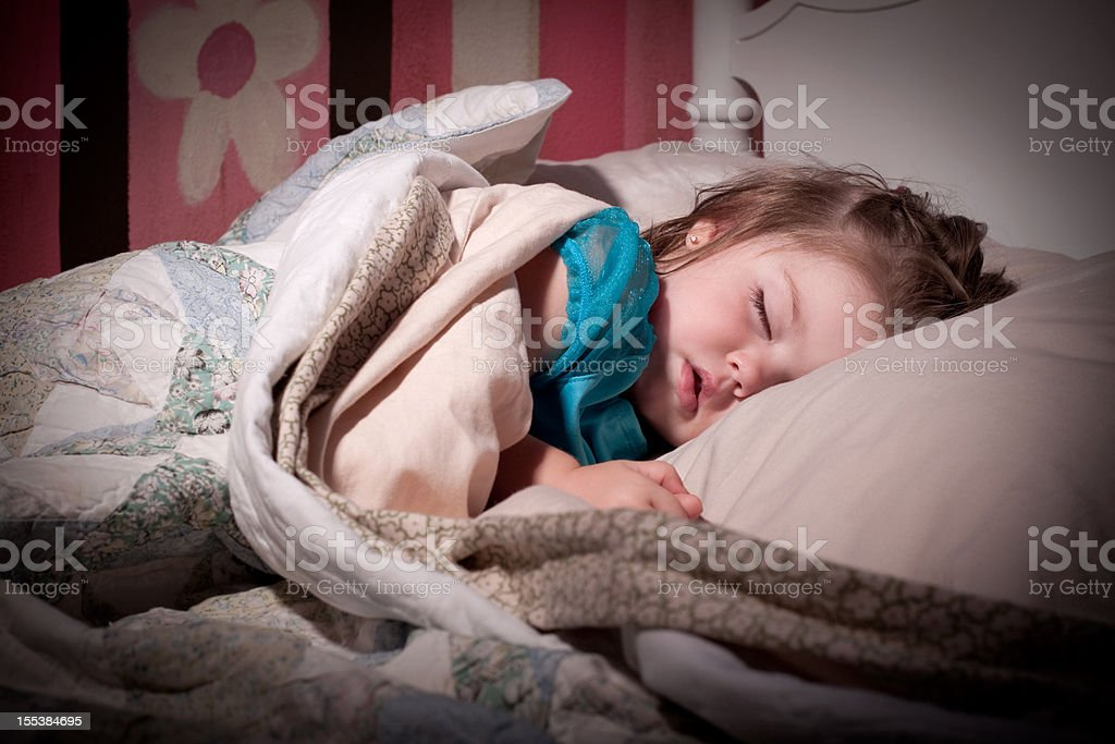 Little girl sleeping on her bed with pink wall behind her royalty-free stock photo