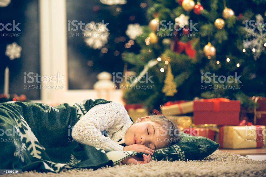 Little girl sleeping under the Christmas tree stock photo