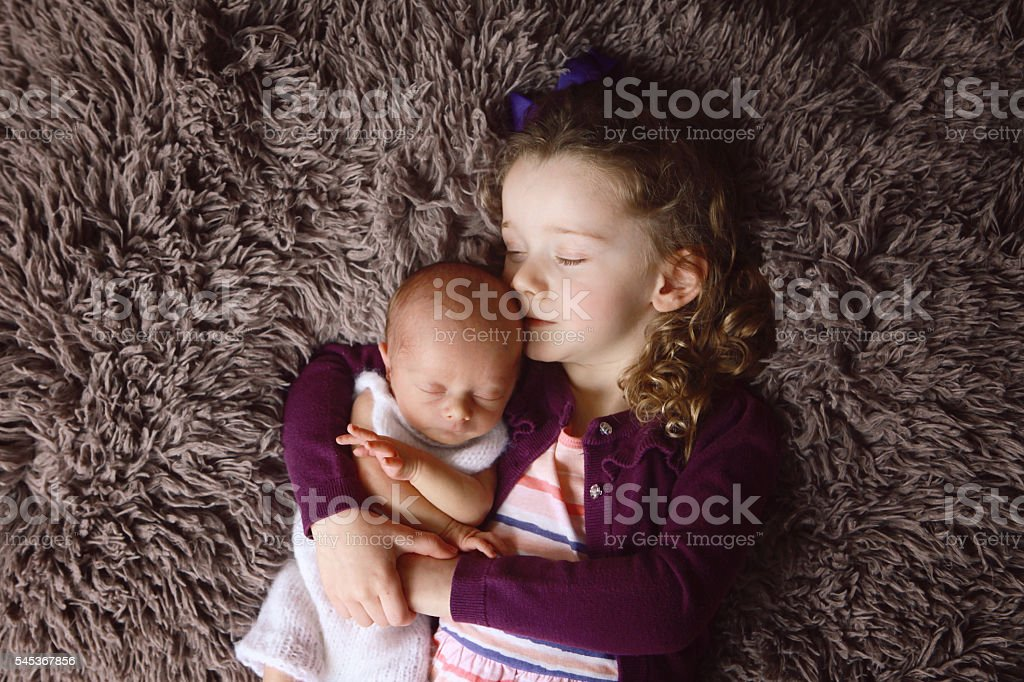 Little Girl Sleeping with her Newborn Brother stock photo