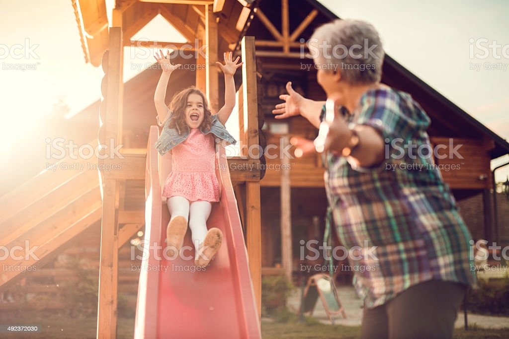 Little girl sliding and having fun outdoors with her grandmother. stock photo