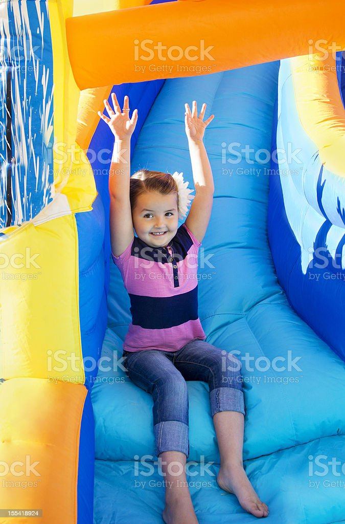 Little Girl sliding down an inflatable Slide royalty-free stock photo