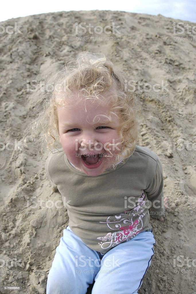 Little girl sliding down sand dune, copy space, summer vacation stock photo