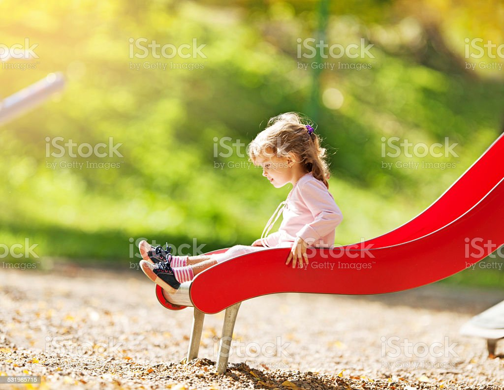 Little girl sliding. stock photo