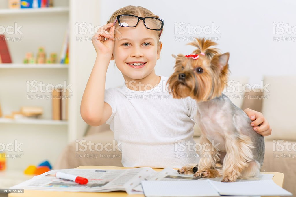 Little girl slightly hugging her dog stock photo