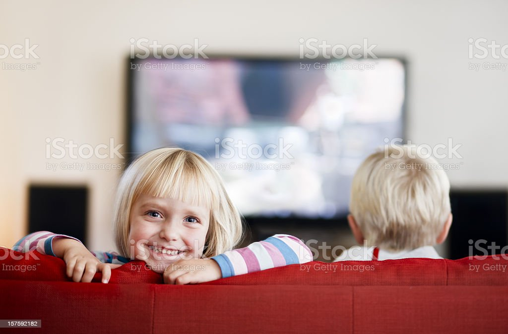 Little girl smiles while little boy watches TV stock photo