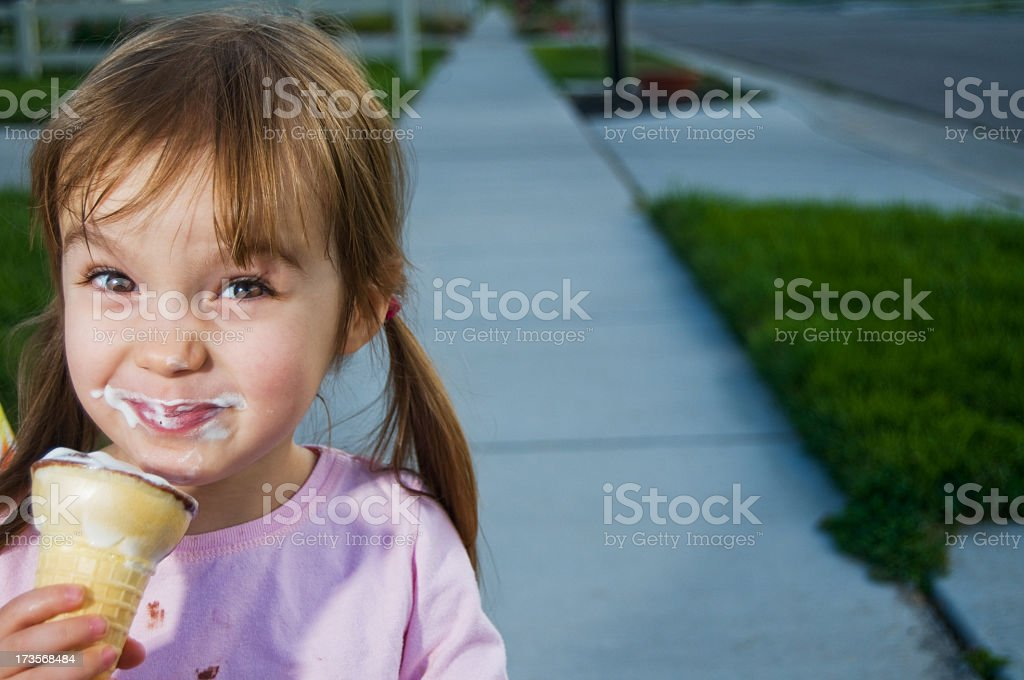 Little girl smiling and eating ice cream in summer royalty-free stock photo