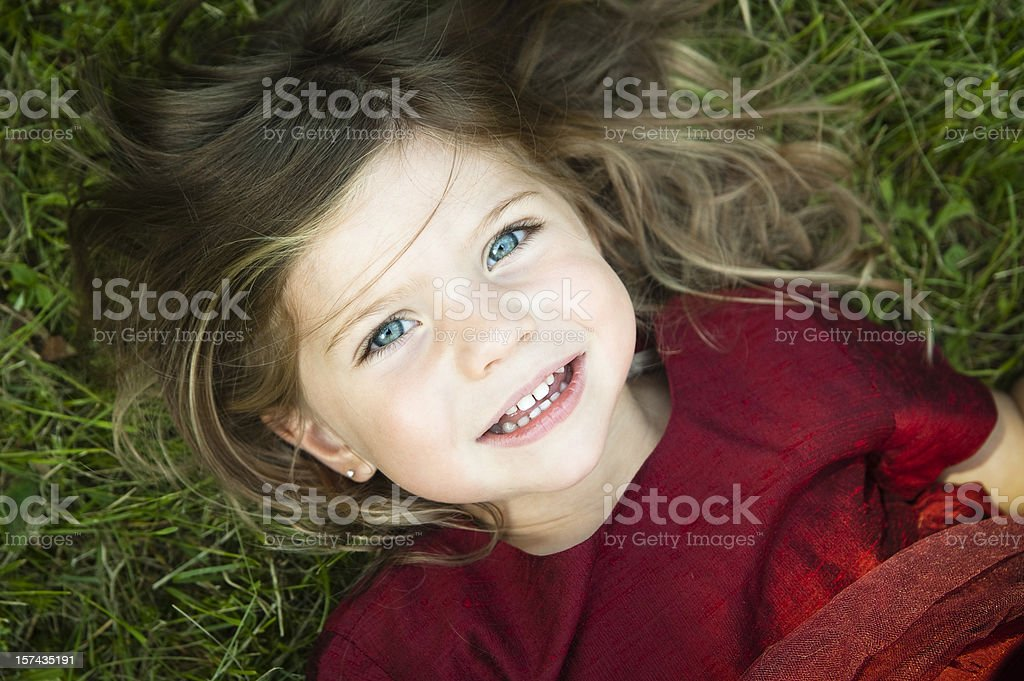 Little girl smiling and lying on grass. royalty-free stock photo