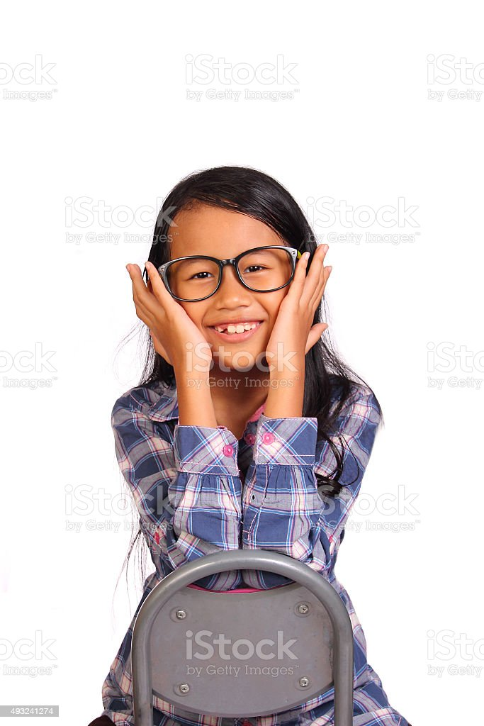 Little Girl Smiling and Touching Her Cheek stock photo